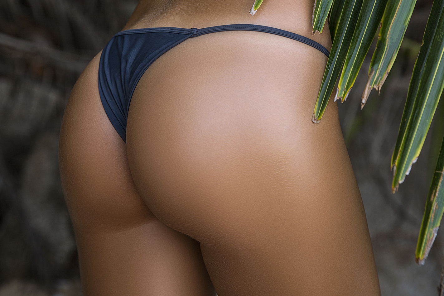 Close-up beautiful luxury slim back of a beautiful woman in a swimsuit posing Against of the palm leaves. Sexy tanned body, flat stomach, perfect figure. Rest on a tropical island. Sexy buttocks.