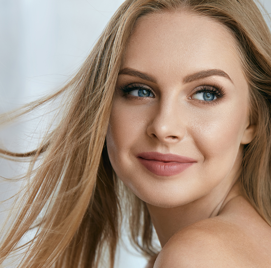 Beautiful Happy Young Woman Smiling Indoors. Portrait Of Attractive Female With Fresh Clean Facial Skin, Healthy Long Blonde Hair And Smile On Gorgeous Face.